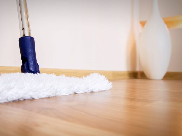 modern white mop cleaning wooden floor from dust