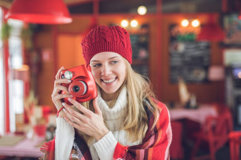 Smiling attractive woman with a red polaroid indoors