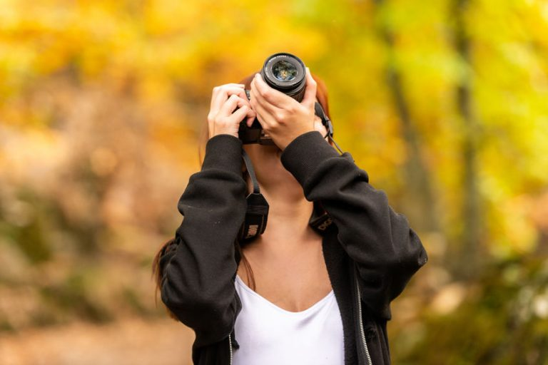 A young woman with reddish hair takes pictures with a reflex camera in an autumnal forest of yellow and ocher colors in Montanchez, Caceres, Extremadura