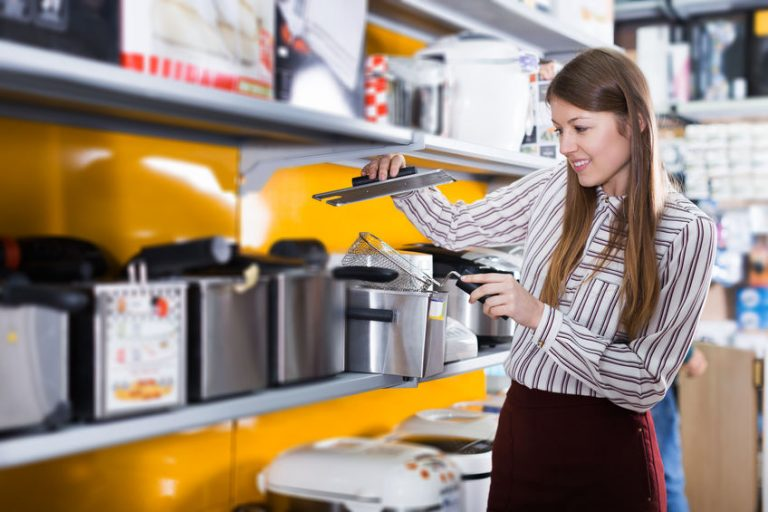 Modern adult housewife buying fryer in domestic appliances section