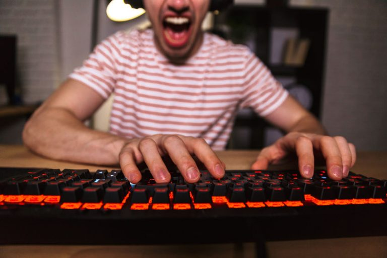 Cropped image of Screaming gamer playing video games on computer while sitting by the table at home