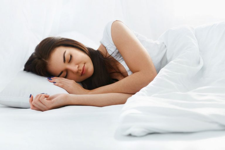 Happy beautiful caucasian girl sleeping on the pillow iin comfortable bed in the bedroom at home in the morning. White bedding. Healthy lifestyle.