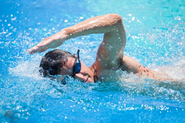 - young man swimming the front crawl in a pool