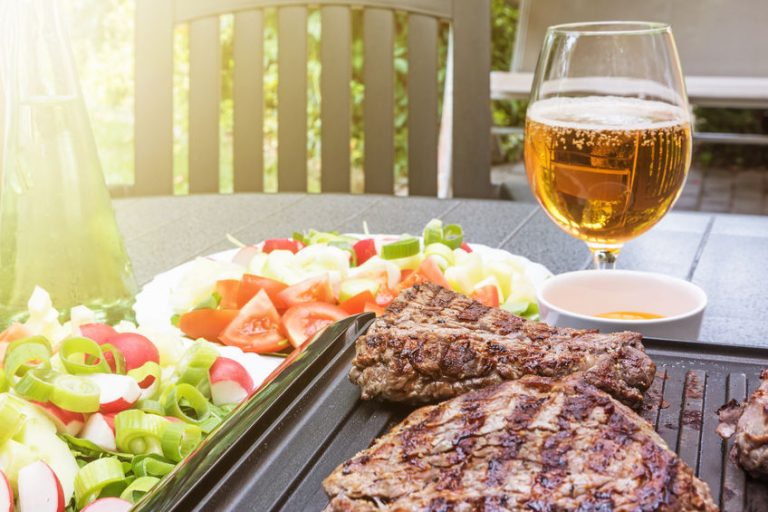 Grill steaks browned on both sides are on an electric stove. Bottle with oil, various kinds of vegetables and glass of beer are standing on the table in the sunshine.