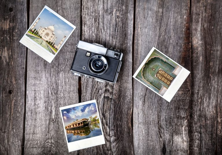Old film camera and polaroid photos with Indian famous landmarks on the wooden background