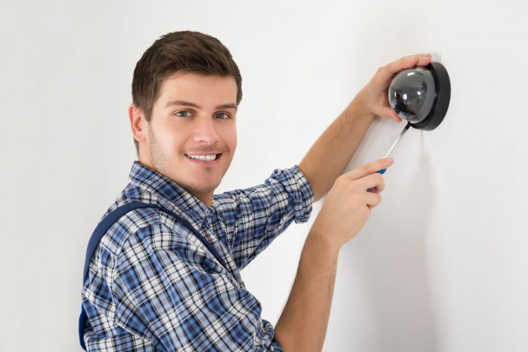 Young Male Technician Installing Surveillance Camera On Wall