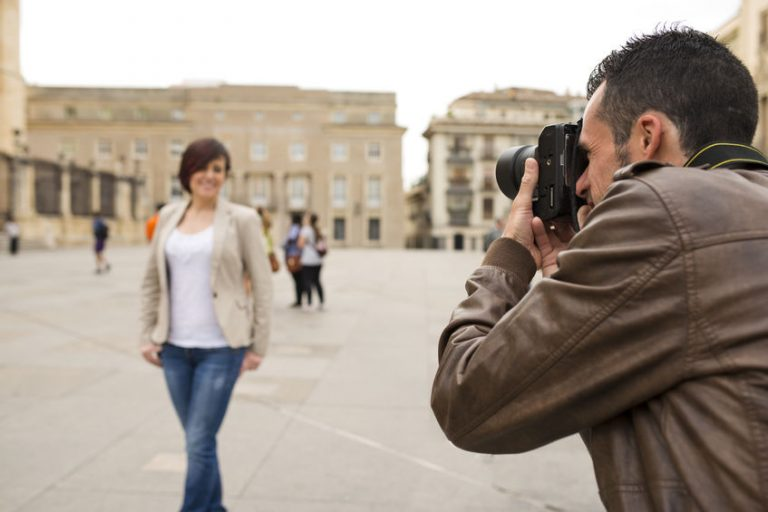 Man taking touritst picture of attractive woman in public place with reflex camera