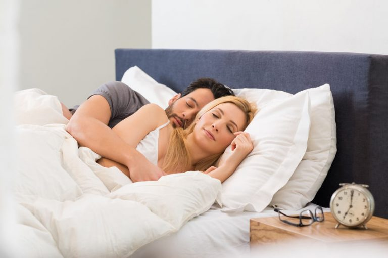 Young adult couple sleeping peacefully on the bed in bedroom. Young man embracing woman while lying asleep. Loving couple sleeping lying in bed at home.